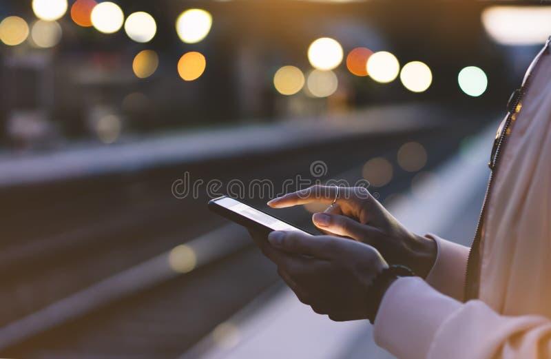 Disfrutar de viaje Mujer joven que espera en la plataforma de la estación en el tren móvil eléctrico de la luz del fondo usando e foto de archivo libre de regalías