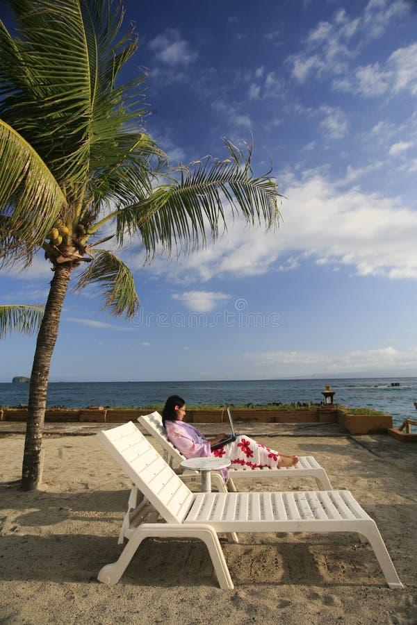 Disfrutar de vida mientras que trabaja en la playa foto de archivo