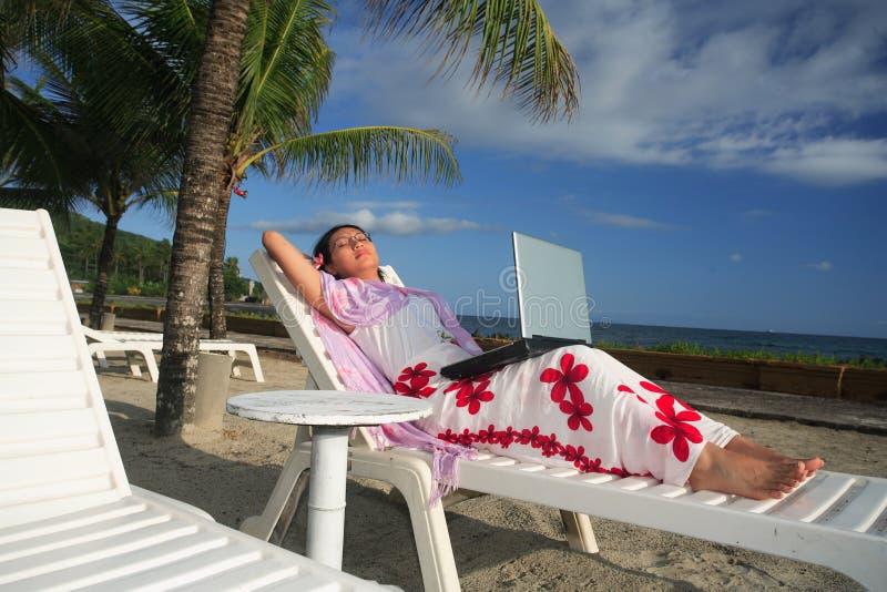 Disfrutar de vida mientras que trabaja en la playa imagen de archivo