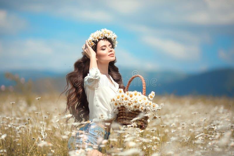 disfrute Chica joven hermosa con la cesta de flores sobre campo de la manzanilla Mujer morena feliz despreocupada con el pelo ond fotos de archivo libres de regalías