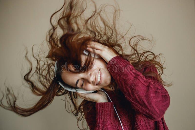 Disfrute de la música Música satisfecha feliz de la mujer joven en auriculares imagen de archivo