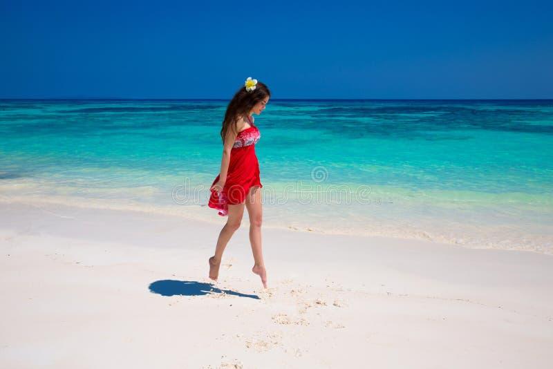 Disfrute de la vida Funcionamiento de salto de la muchacha hermosa en la playa exótica con imagenes de archivo