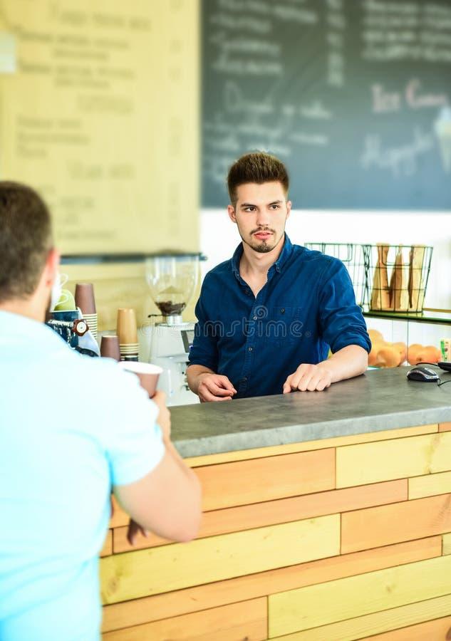 Disfrute de su bebida El inconformista elegante hermoso de Barista comunica con el visitante del cliente Café servido a ir El hom foto de archivo libre de regalías