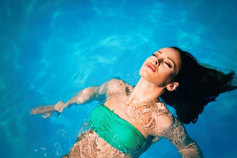 Disfrute del verano Mujer que se relaja en el agua de la piscina imágenes de archivo libres de regalías