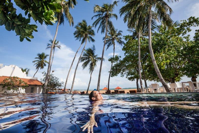 Disfrute del verano tropical Mujer que se relaja en el agua de la piscina imagenes de archivo