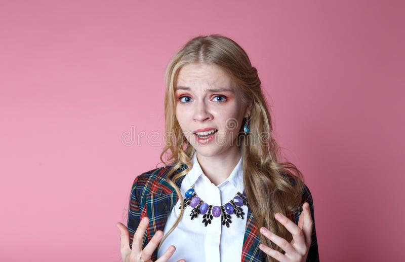 Disgruntled and angry blonde girl with long curly hair in stylish plaid jacket spreads her hands, what`s going on. Disgruntled and angry blonde girl with long stock image