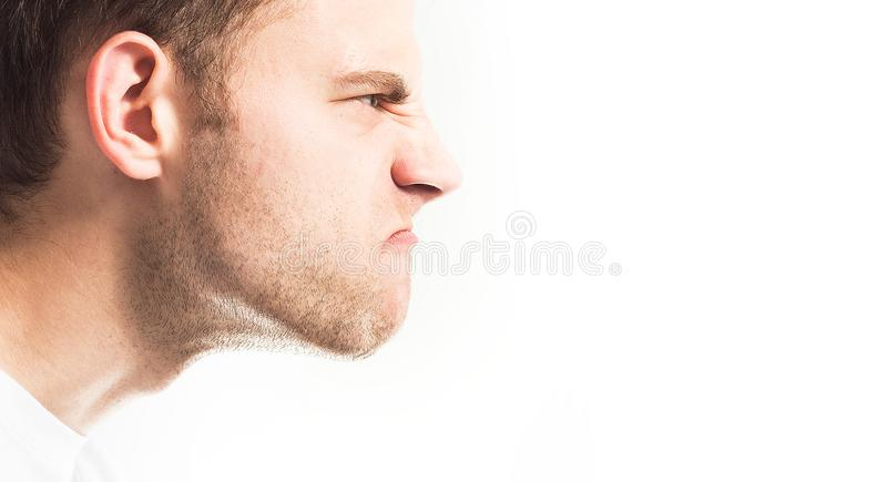 Disgruntled, angry face of a man on a white background in profile royalty free stock photography