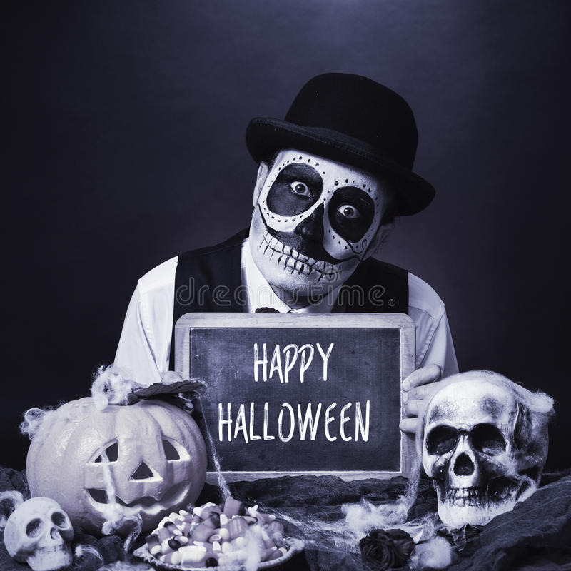 Disguised man with chalkboard with text happy halloween, b&w. A man with calaveras makeup, wearing bowler hat, shows a chalkboard with the text happy halloween stock photography