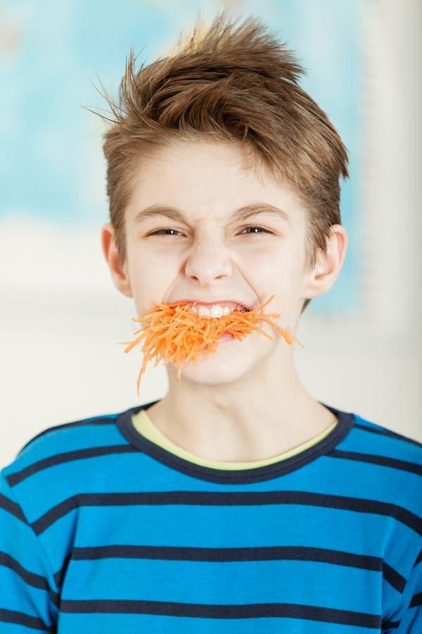 Disgusted молодой мальчик с ртом полным моркови стоковые фотографии rf