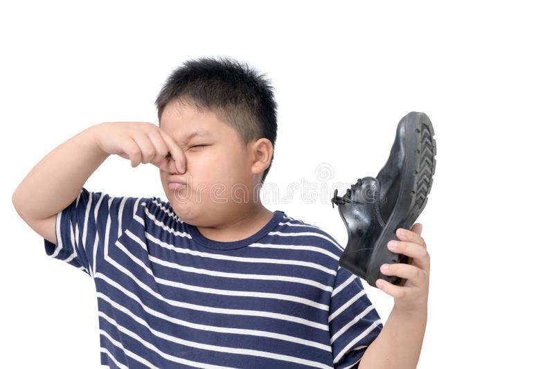 Disgusted boy holding a pair of smelly leather shoes royalty free stock photography