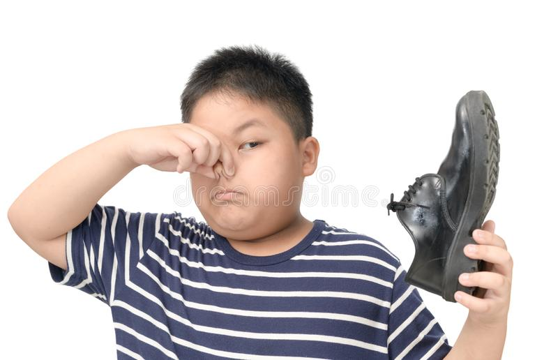 Disgusted boy holding a pair of smelly leather shoes royalty free stock photo