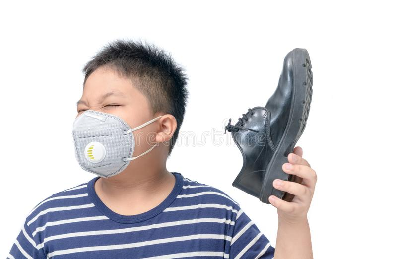 Disgusted boy holding a pair of smelly leather shoes stock images