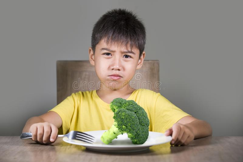 Disgusted child refusing to eat healthy green broccoli feeling upset in kid nutrition education on healthy fresh food and young stock images
