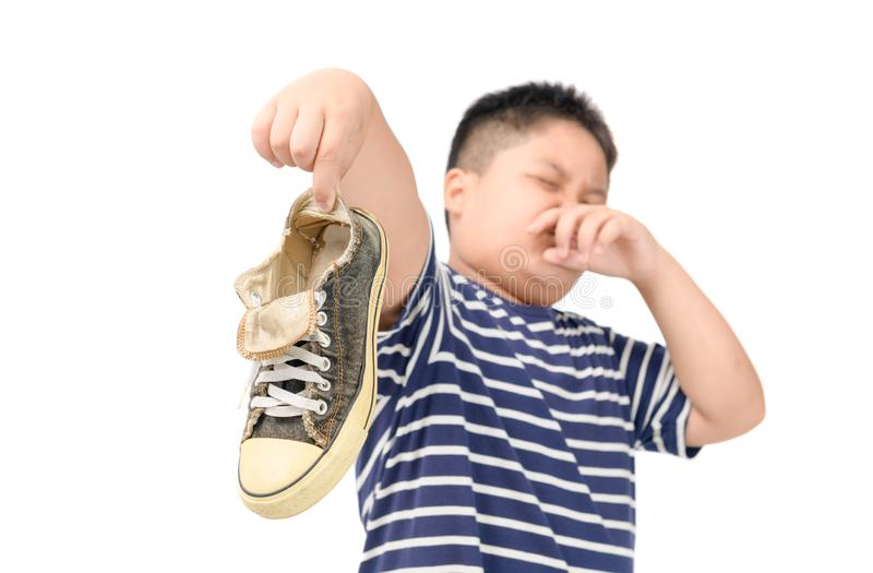 Disgusted fat boy holding a pair of smelly shoes royalty free stock images
