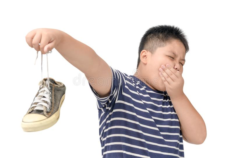 Disgusted fat boy holding a pair of smelly shoes royalty free stock photography