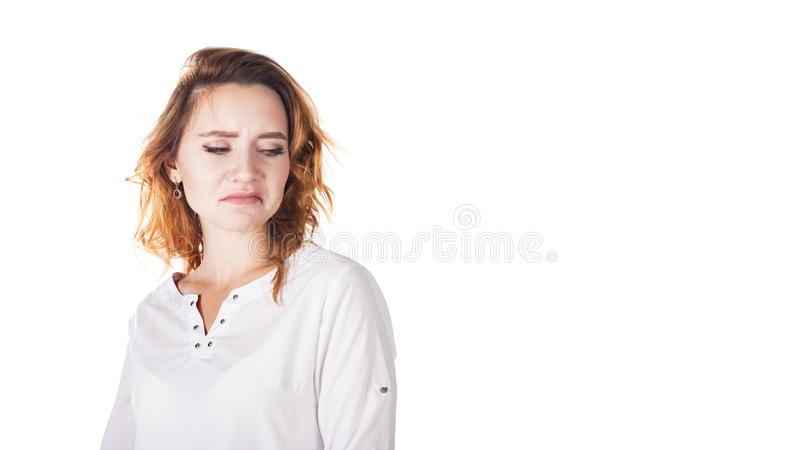 Disgusted and frowning young woman on a white background royalty free stock photo