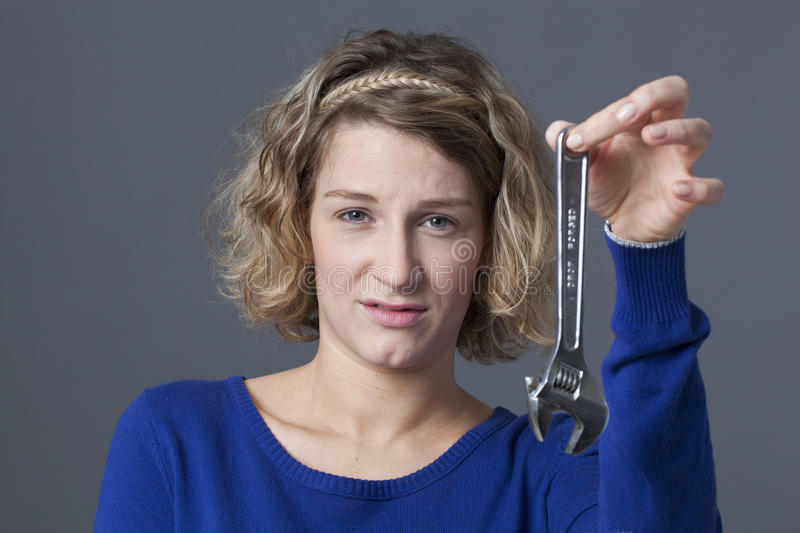 Disgusted 20s woman holding wrench for mechanics DIY. Female DIY concept - disgusted young blond woman holding wrench as symbol of manual work and mechanics royalty free stock photo