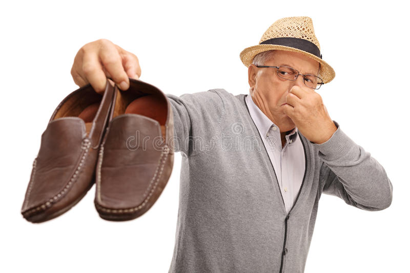 Disgusted senior holding stinky shoes stock photos