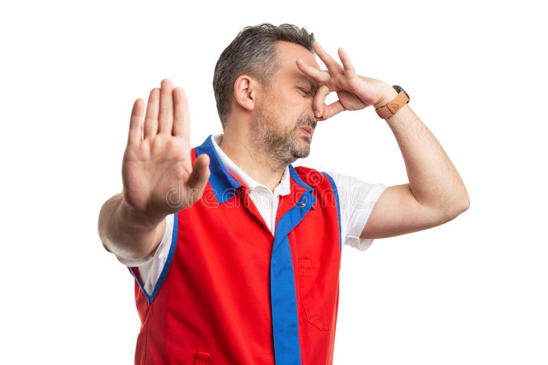 Supermarket employee making gross smell gesture. Disgusted supermarket or hypermarket male employee making gross smell gesture with palm and holding nose royalty free stock image