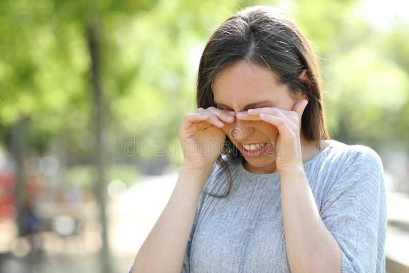 Disgusted woman rubbing her eyes in a park royalty free stock image