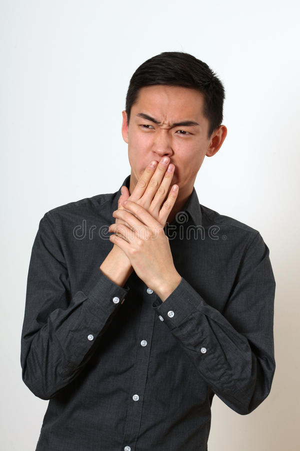 Disgusted young Asian man covering his mouth with hands royalty free stock photo