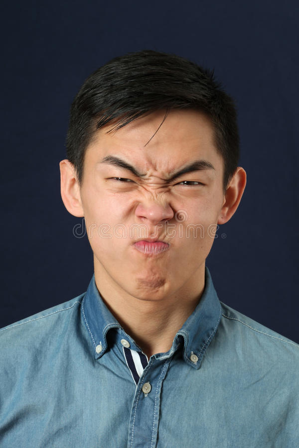 Disgusted young Asian man making face and looking at camera stock photography