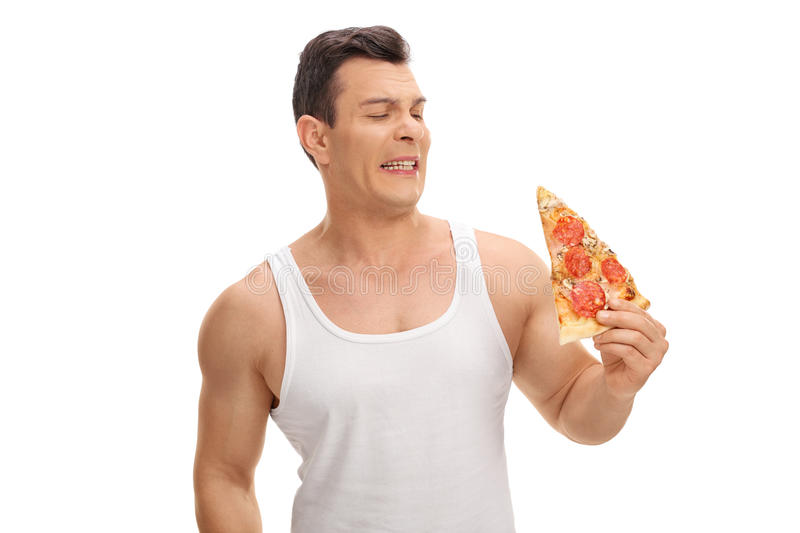 Disgusted young guy looking at a slice of pizza royalty free stock photos