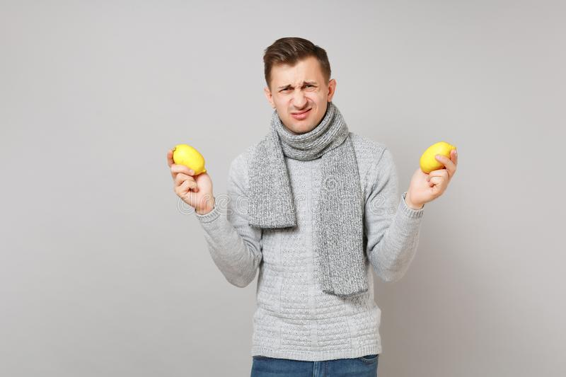 Disgusted young man in gray sweater, scarf holding lemons on grey wall background studio portrait. Healthy stock images
