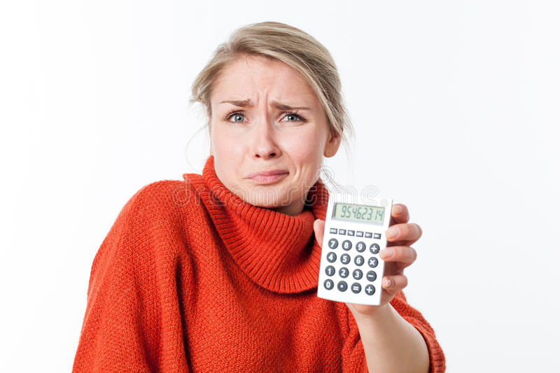 Disgusted young woman holding a calculator for fear or maths royalty free stock image