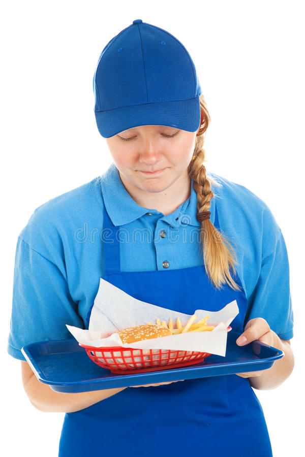 Disgusting Fast Food Meal. Teenage fast food worker disgusted by the burger and fries she's serving. Isolated on white royalty free stock photo