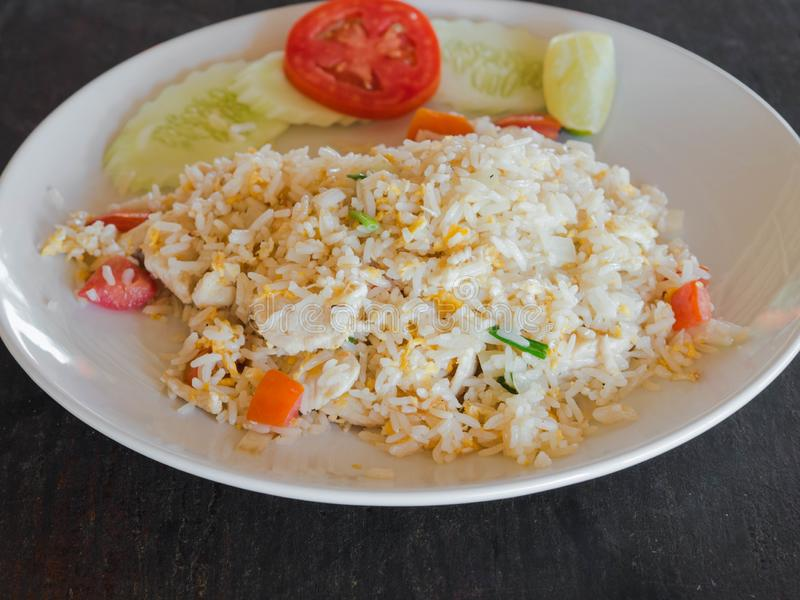 Dish of Asian cuisine - fried white rice with egg, chicken meat and vegetables on a white plate on the wood table in a Thai. Dish of Asian cuisine - fried white stock photo