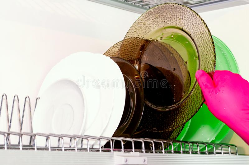 Dish dryer in the closet. White background. Plates of different colors. Cleaning, cleanliness. Dish dryer in the closet. White background. Plates of different stock photos