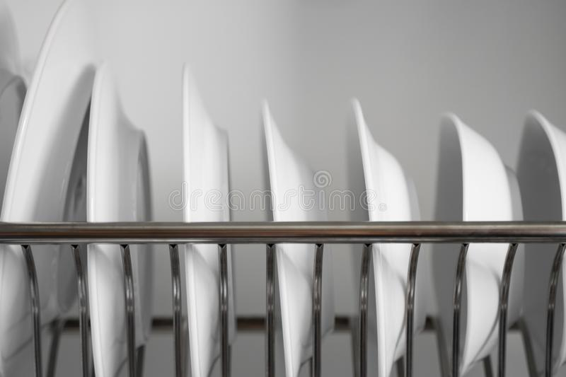 Dish drying metal rack with big nice white clean plates. Traditional comfortable kitchen. Open white dish draining. Closet with wet dishes of glass and ceramic royalty free stock image