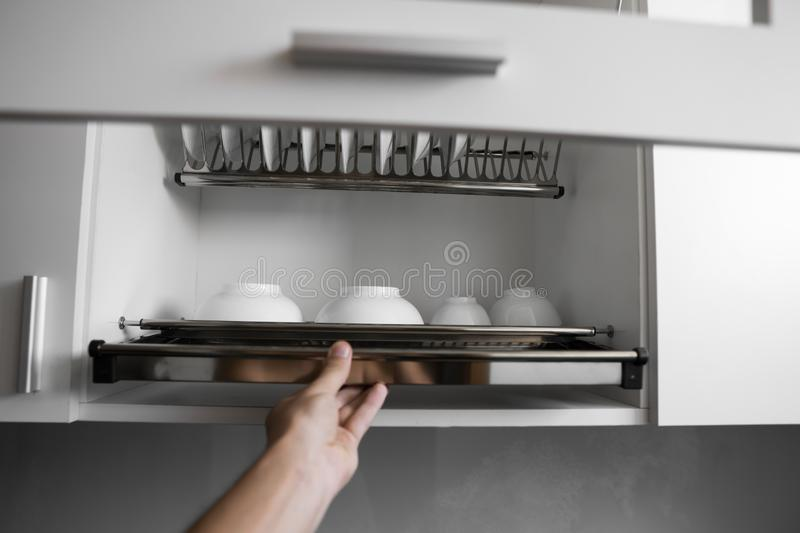 Dish drying metal rack with big nice white clean plates. Traditional comfortable kitchen. Open white dish draining. Closet with wet dishes of glass and ceramic stock photo