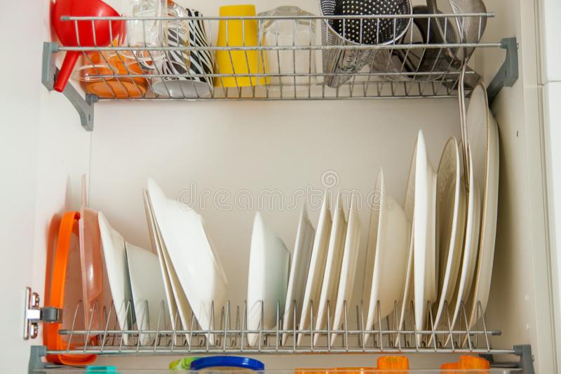 Dish drying metal rack with big nice white and light yellow clean plates on blurred background. royalty free stock photography
