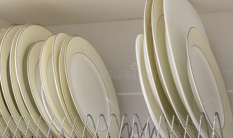 Dish drying metal rack with big nice white and light yellow clean plates on blurred background. Traditional comfortable kitchen stock photo