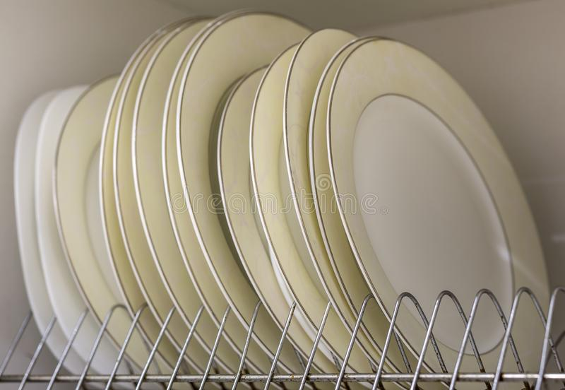 Dish drying metal rack with big nice white and light yellow clean plates on blurred background. Traditional comfortable kitchen stock image
