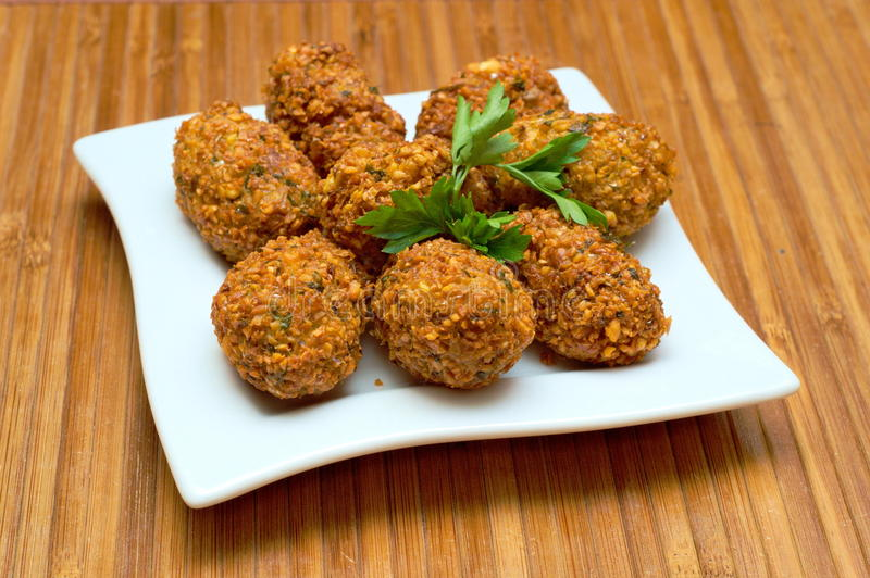 Dish of fried Falafels. Dish of tasty deep-fried chickpeas balls decorated on top with leaves of fresh parsley. This Middle-Eastern appetizer is standing on royalty free stock photos