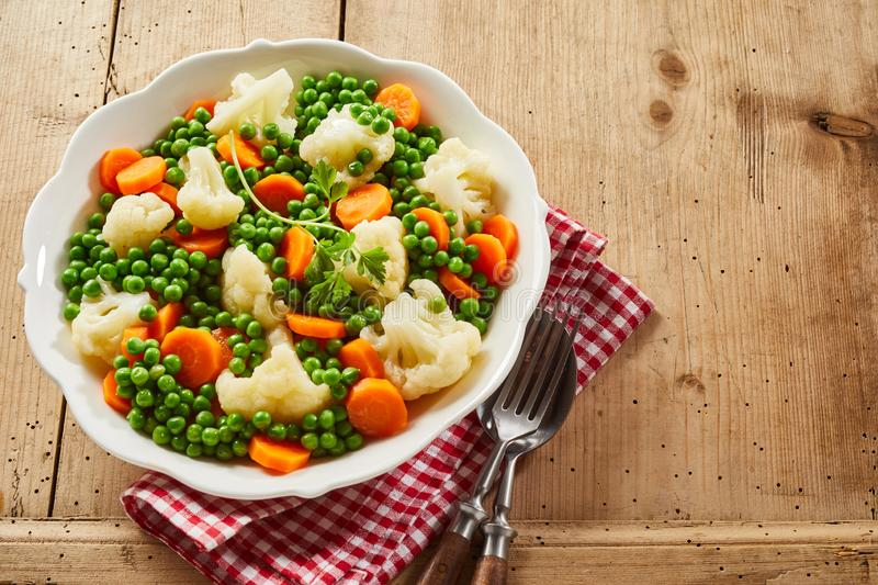 Dish of fresh tender young vegetables. With a mix of diced carrots, peas and cauliflower viewed high angle on wood with copy space and cutlery stock images