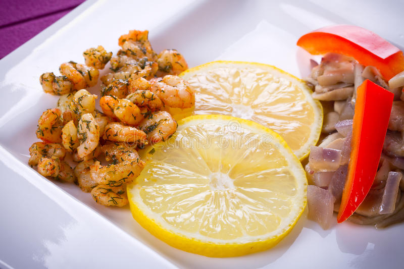 Dish with fried prawns and lemon. Starter with fried prawns with lemon, mashrooms and brown bread royalty free stock image
