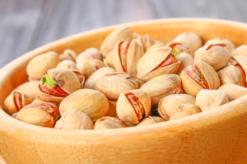 Dish full of pistachios with more pistachios on side. Dish full of pistachios with more pistachios on side stock photo