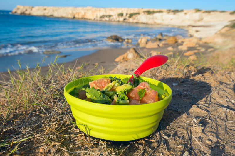Dish with gourmet vegetarian salad. On the beach. Healthy eating while traveling, hiking. Sunny day on Cyprus royalty free stock photo