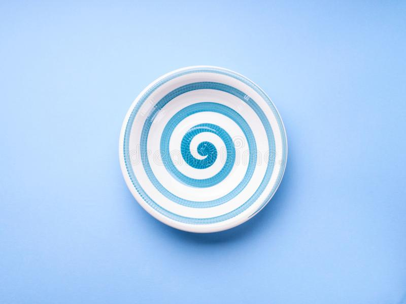 Dish with hypnotizing spiral on pastel blue royalty free stock photo