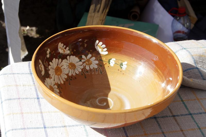 Light brown dish made by masters in Latvia. A dish of light brown color, decorated with daisies and made by masters from Latvia stock photos