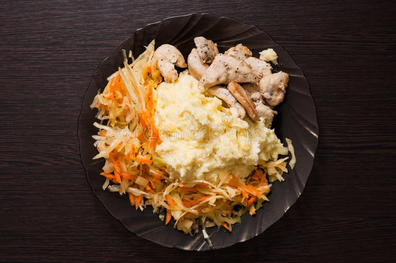 Dish of mashed potatoes, cabbage and carrot salad, fried diet chicken breast royalty free stock photo