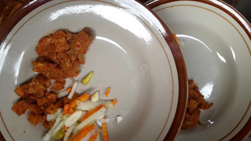 Dish with a menu of beef or commonly called rendang with pickles stock image