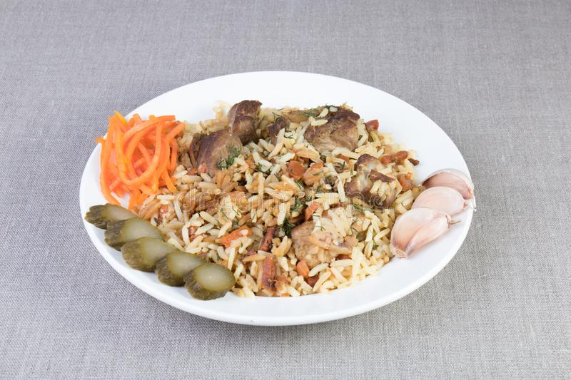 Dish of pilaf with beef, carrots, cucumber, garlic on a plate stock images