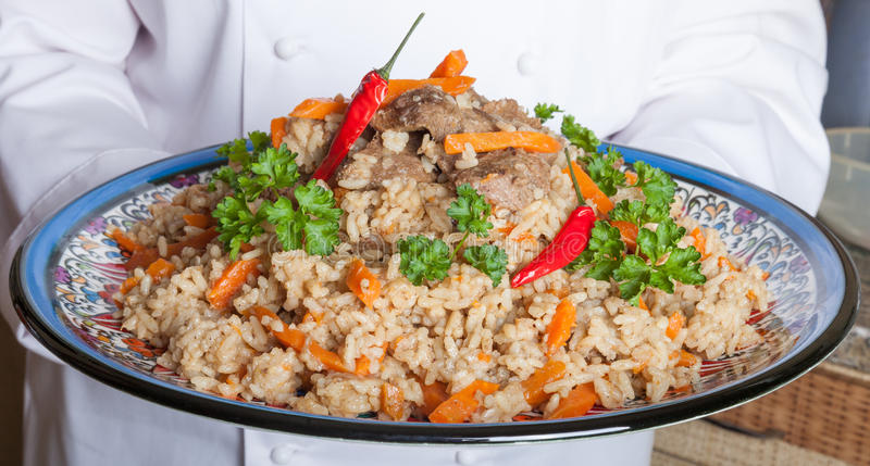 Dish with pilaf in the hands of the cook royalty free stock images