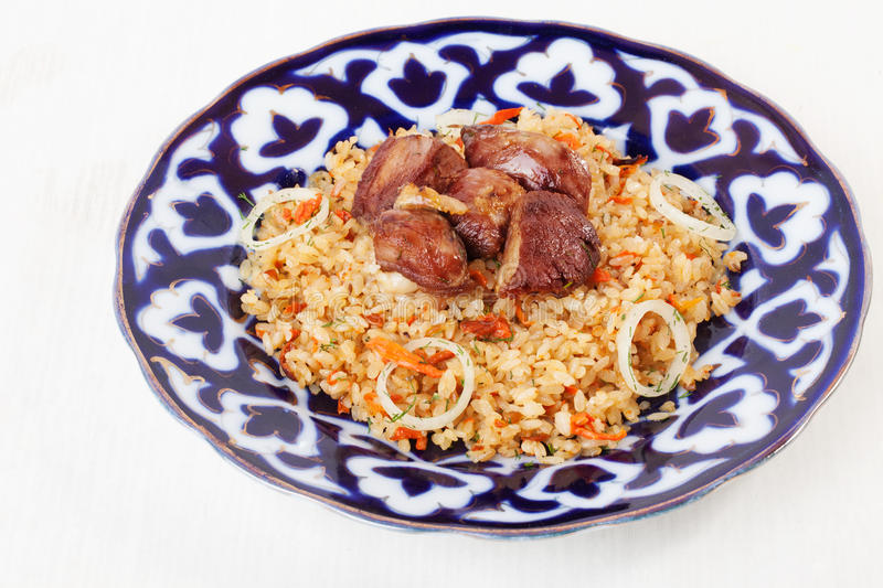 Dish with pilaf Uzbek dishes, garlic, onions, carrots, tomatoes, beef, meat, large, on a white background. For the menu royalty free stock images