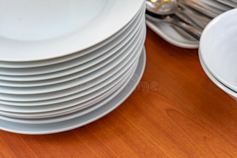 Dish, plates, bowls, spoon, fork are arranging and preparing on wood table for buffet lunch or dining., have space for text below stock photos